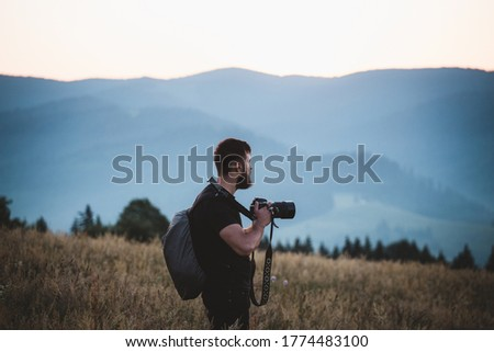 Nature Wildlife Photographer Working in the Field. Young Photographer Taking Pictures on the pasture while wearing his gear backpack. Scenic sunrise at dawn in Bucovina, Romania.