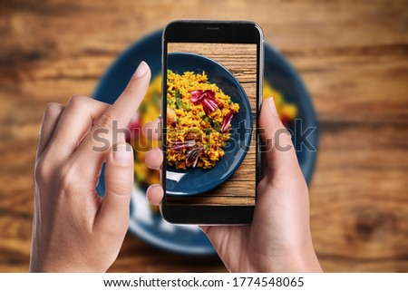 Blogger taking picture of delicious pilaf with chicken and vegetables at table, closeup. Food photography