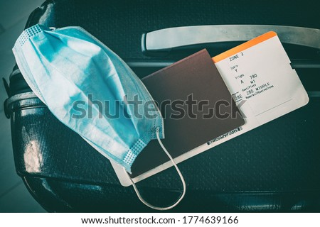 COVID-19 travel restriction due to corona virus mask wearing obligatory in airport and airplane flights to Europe, Asia. Passport, ticket and suitcase ready for holidays. #1774639166