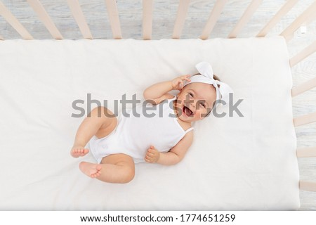 baby girl 6 months old lies in a crib in the nursery with white clothes on her back and laughs, looks at the camera, baby's morning, baby products concept #1774651259
