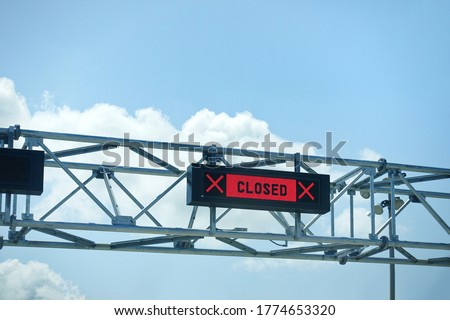 LED closed sign at country border gate against blue sky. Border closed in coronavirus pandemic lockdown to restrict non-essential travel. Multiple countries ban UK travellers due to new covid variant. Royalty-Free Stock Photo #1774653320