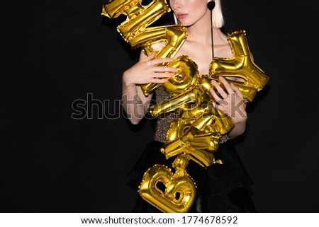 Gorgeous woman in glittering dress holding letter shaped balloons while wishing you happy birthday at party against black background