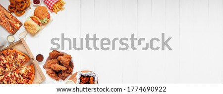 Selection of take out and fast foods. Corner border banner. Pizza, hamburgers, fried chicken and sides.  Top down view on a white wood background with copy space. Royalty-Free Stock Photo #1774690922