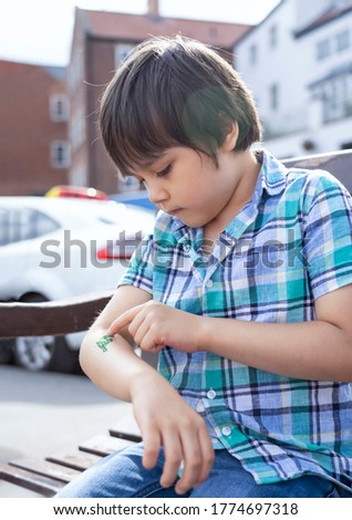 Candid shot kid sitting on bench looking at green glitter on his arm, Child boy siting outdoor playing  tattoo on his own with blurry cars on the road in the sunny summer  Royalty-Free Stock Photo #1774697318