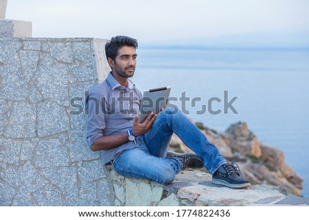Man thinking while using pad looking to blue sky while sitting on a concrete bridge above the sea taking deep breath enjoying freedom at sunset sea on background. Melancholic thoughtful person #1774822436