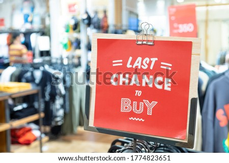 Red Last chance to buy sign inside cloth store during mid year sale, discount period. Department store and shopping concept.