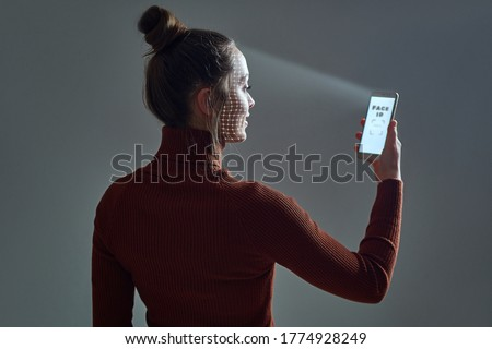 Woman scans face using facial recognition system on smartphone for biometric identification. Future high tech technology and face id Royalty-Free Stock Photo #1774928249