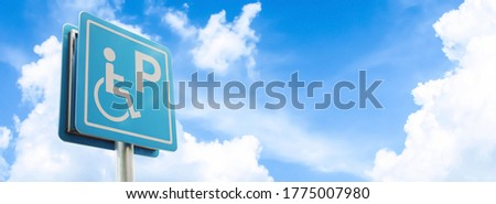 Closeup of handicapped parking place sign on blue sky background.