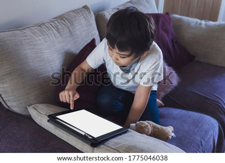 Cropped shot kid sitting on sofa watching cartoons on tablet,6-7 year old boy playing game on touch pad, Cute Kid having fun and relaxing on his own in living room, New normal lifestyle