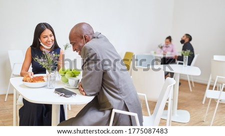 Business people are sitting at separate tables in the cafeteria for keeping distance because of Covid-19 Royalty-Free Stock Photo #1775087483
