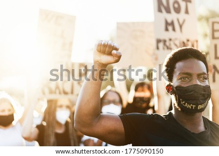 Young black man wearing face mask during equal rights protest - Concept of demonstrators on road for Black Lives Matter and I Can't Breathe campaign - Focus on man's face