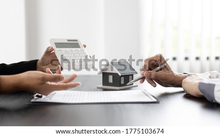 Real estate agent talked about the terms of the home purchase agreement and asked the customer to sign the documents to make the contract legally, Home sales and home insurance concept. Royalty-Free Stock Photo #1775103674