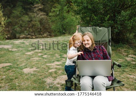 Communication with family online on laptop near fire in nature. Homeschooling, freelance job. Mother work on Internet with kid outdoors. Quarantine, closed nursery school during coronavirus outbreak.
