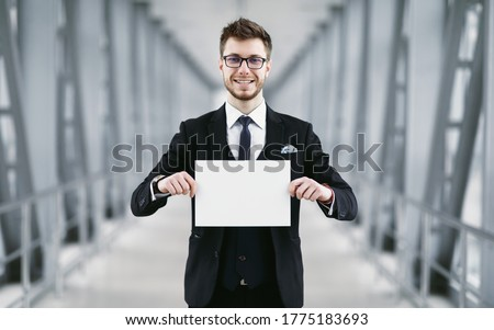 Welcome. Man in glasses holding empty signboard for name at international airport meeting point, blank space
