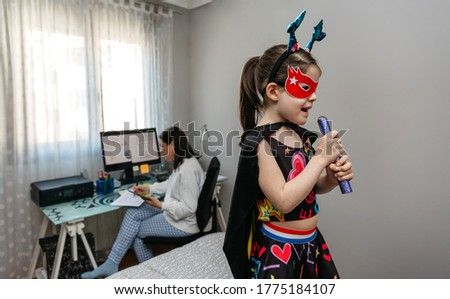 Little girl singing in disguise while her mother teleworking in the bedroom Royalty-Free Stock Photo #1775184107