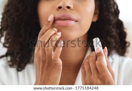 Lip Care. Unrecognizable black woman applying moisturising chapstick on lips, cropped image, closeup Royalty-Free Stock Photo #1775184248