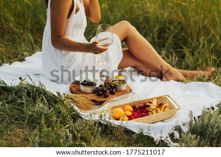 Cropped picture of a girl sitting on a grass on nature. Concept of having picnic in a city park during summer holidays or weekends. Girl in a summer dress, sitting with a glass of wine at a picnic.