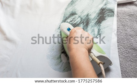 Women wearing T-shirt ironing clothes on ironing board in laundry room at home. The concept of caring for the home, helping men in household chores. woman uses an iron to iron the child's clothes. #1775257586