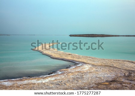The concept of active and photo tourism. Israel. Dim winter day over the Dead Sea. Skies merge with sea on horizon. Evaporated salt protrudes above water