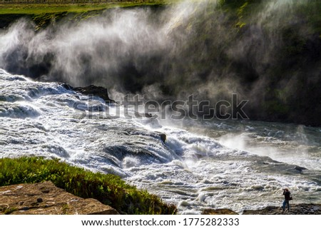 """Iceland. Tourist - photographer with photo bag  takes pictures of burrowing waterfall. Gullfoss """"Golden Falls"""" - the waterfall fed by glacial water. The concept of extreme and photo tourism"""