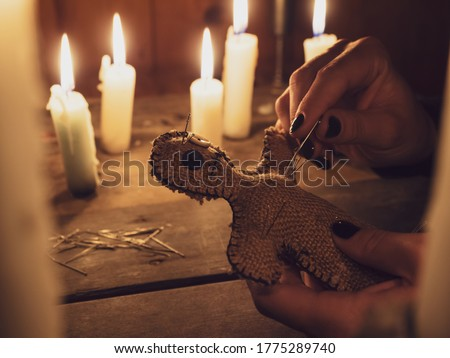 A girl pierces a voodoo doll with needles, close-up. Esoteric and occult rituals on a wooden table in a dark room with many candles. The concept of revenge, causing harm to a rival. Magic background. #1775289740