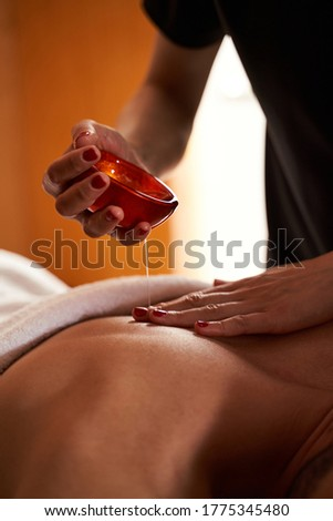 Cropped photo of hands of massage therapist touching the back of a person while pouring oil on it