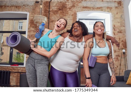 Cheerful afro american woman hugging her friends while laughing together and being prepared for sport lesson Royalty-Free Stock Photo #1775349344