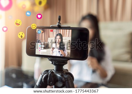 Asian businesswoman working from home live video interaction with customers using camera device vlogging selling make up products, viral internet social media influencer interacting to live audience Royalty-Free Stock Photo #1775443367