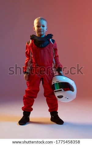 Cool boy child racer with helmet, standing in neon light. Kart racing school poster. Competition announcement Royalty-Free Stock Photo #1775458358