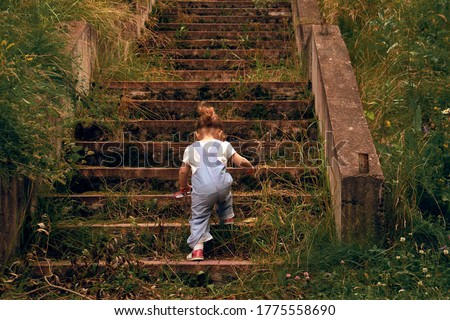 A little girl, 2 years old, with a ponytail and in a jumpsuit, climbing up the steps of the old stone, overgrown grass stairs. Concept of overcome. Cottagecore aesthetics concept. Royalty-Free Stock Photo #1775558690
