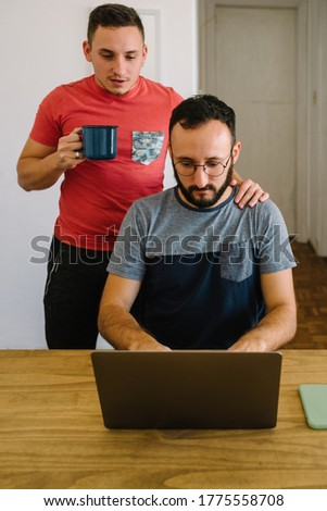 Stock photo of two caucasian adult men looking at a laptop thinking. One of them is standing holding a mug and has his arm on the others shoulder.