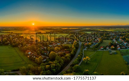 Sunset over a little town, orange sunbeams illuminate the houses. Beautiful time of a springday. Royalty-Free Stock Photo #1775571137