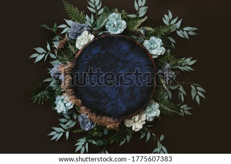 Newborn digital background - brown wooden bowl with green leaves wreath,  teal flowers and blue faux fur. Royalty-Free Stock Photo #1775607383