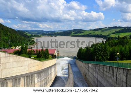 Water overflow in the dam. Opened water dam. Dam and water reservoir in Niedzica was created in order to reduce flood culminations.  Czorsztyn lake, southern Poland, Europe.  #1775687042