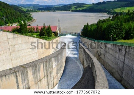 Water overflow in the dam. Opened water dam. Dam and water reservoir in Niedzica was created in order to reduce flood culminations.  Czorsztyn lake, southern Poland, Europe.  #1775687072