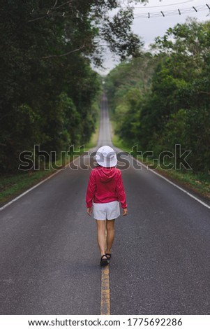 A woman wearing a red hood and white hat walks on asphalt road in a quiet forest. There is a steep hill with a white border and a yellow centerline. Beside the road, there are grass and green trees. #1775692286
