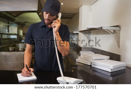 Handsome pizza delivery man taking an order over the phone in a commercial kitchen #177570701