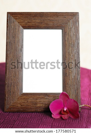 Empty picture frame and orchid on the table