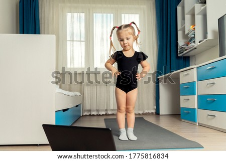 online rhythmic gymnastics. girl preschooler doing rhythmic gymnastics with a trainer online