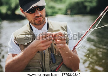 Young fisherman fishing on lake or river. Picture of process using some lure for fishing line before putting it into water for catching delicious fish. Serious brutal fisherman on picture.