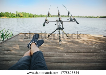 Young fisherman fishing on lake or river. Picture of relaxed guy sitting on pier alone and looking at three fish-rods. Water hunting hobby, time and process. View of fisherman's eyes.