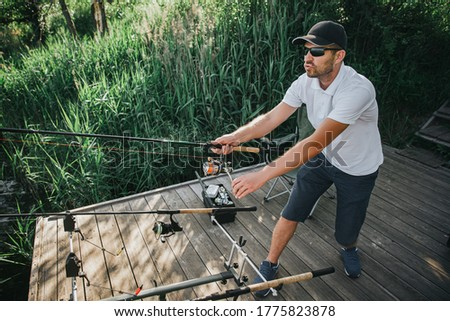 Young fisherman fishing on lake or river. Picture of fishing process. Guy holding two rods in hands and fishing. Stand alone at water pier.