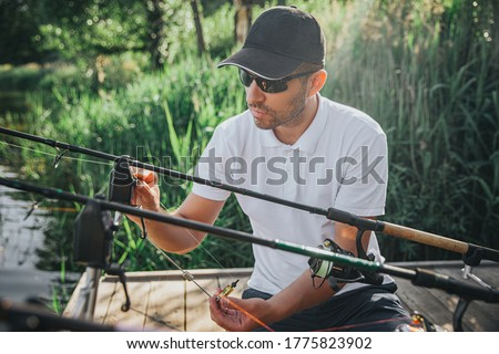 Young fisherman fishing on lake or river. Picture of guy in cap and sunglasses adjusting reel and lure with rods before fishing. Sitting alone in front fishing equipment. Daylight and sunny day.