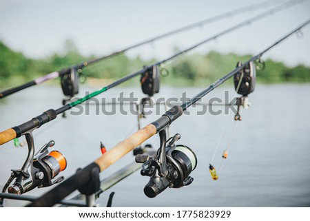 Young fisherman fishing on lake or river. Picture of three rods with full equipments during fishing time. No people beside. Reel and lure. Sunny beautiful day.
