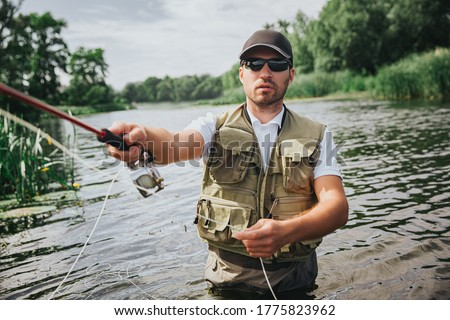 Young fisherman fishing on lake or river. Picture of man doing active fishing with holding rod in hand. Stand alone in middle of river or lake. Serious concentrated guy fishing.