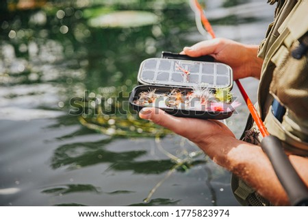 Young fisherman fishing on lake or river. Close up picture of guy holding some plastic artificial lures for catching fish in opened box. Stand alone in water and hold fishing rod.