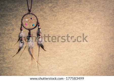 Leather dream catcher on sepia tone background, left copy space