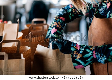 woman preparing delivery food inside takeaway restaurant - Worker preparing paper bags with food for home order service #1775839517