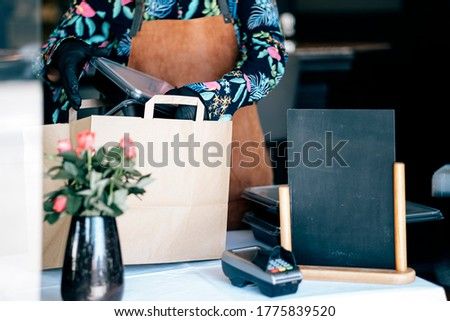 woman preparing delivery food inside takeaway restaurant - Worker preparing paper bags with food for home order service #1775839520