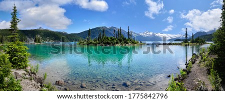 Panoramic view of glacial mountain Garibaldi lake with turquoise water on sunny summer day.islands with firs in the middle of the lake.  Garibaldi provincial park near Whistler, BC, Canada. Royalty-Free Stock Photo #1775842796